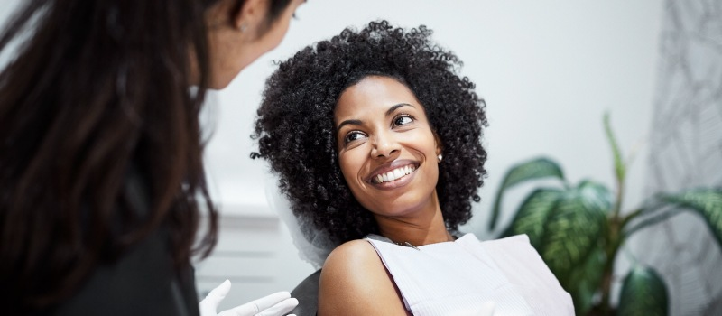 Curly haired woman smiles before receiving dental sedation at Seaport Family Dentistry in Liberty, MO