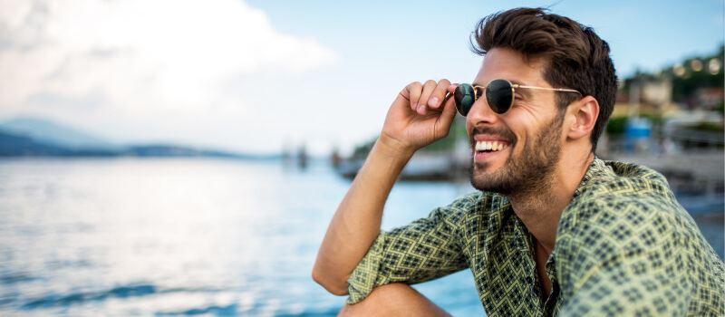 Brunette man wearing sunglasses smiles at the lake after restoring his smile with dental implants
