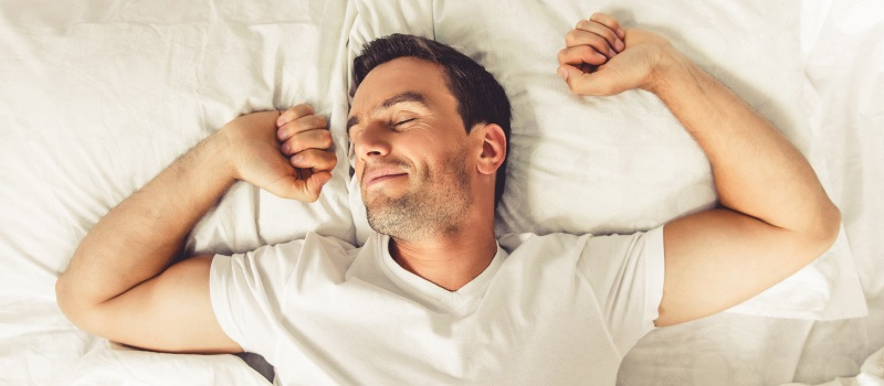 Man with sleep apnea wakes up refreshed after improving his sleep with Dental Sleep Medicine