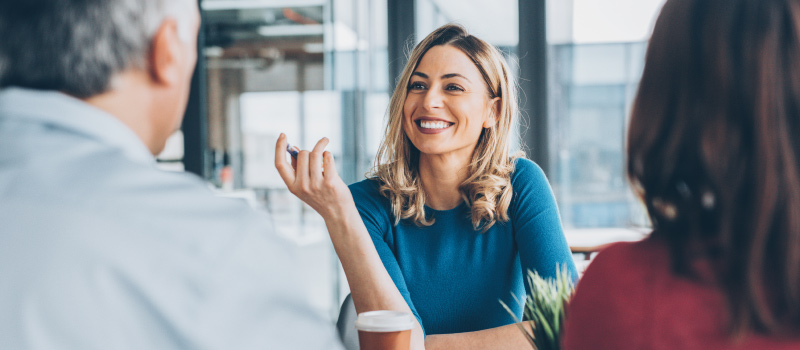 Business woman smiles at work to boost her productivity and improve her mood