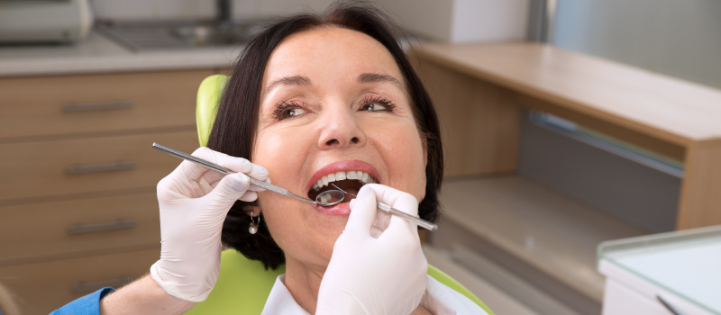 Brunette woman sits in a dental chair during a scaling and root planing procedure